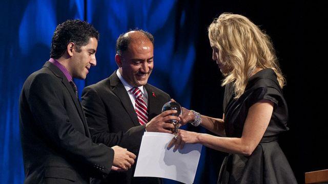 آرش (وسط) و کامیار علایی (چپ) جایزه الیزابت تیلور را از شارون استون میگیرند
