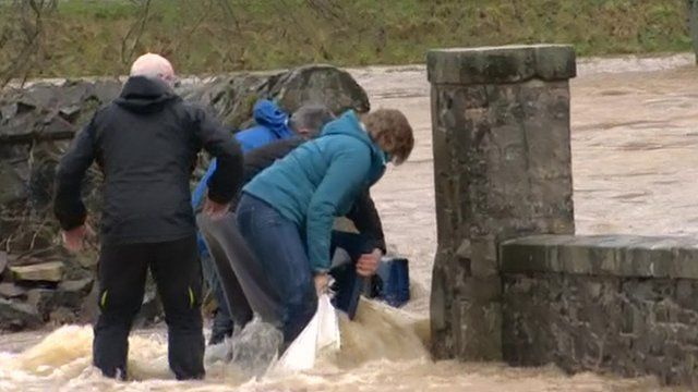 People attempting to block a gap in the wall to prevent floodwaters getting in