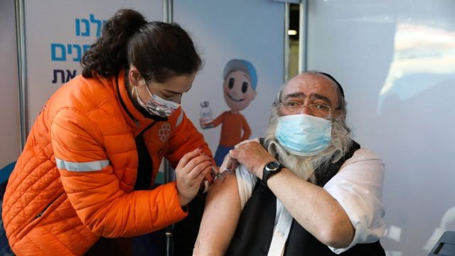 Israeli nurse vaccinates Orthodox Jewish man, Jerusalem (28 Dec)