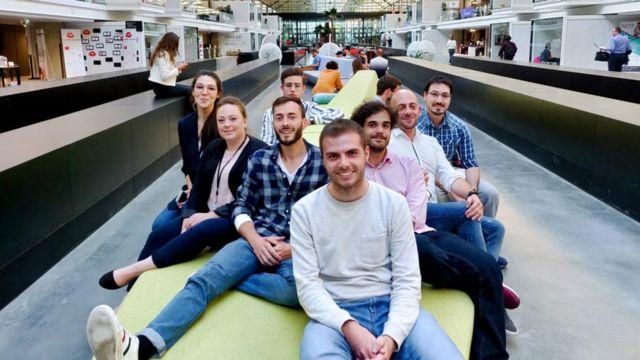 Funcionários da Advitam sorrindo e sentados em banco dentro de prédio corporativo