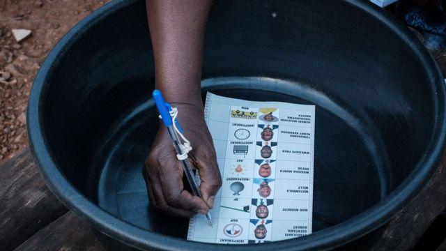 Pessoa escrevendo em cédula de votação