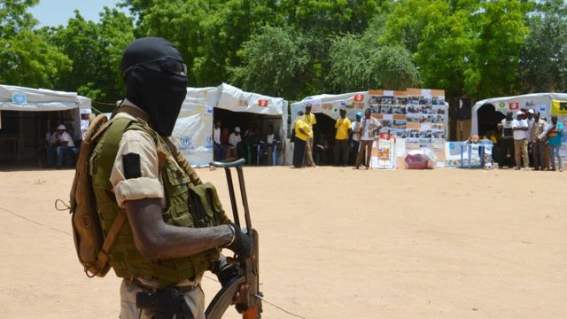 Un soldat nigérien monte la garde près des stands d'information dans un camp pour personnes déplacées à Diffa, au Niger, en 2016