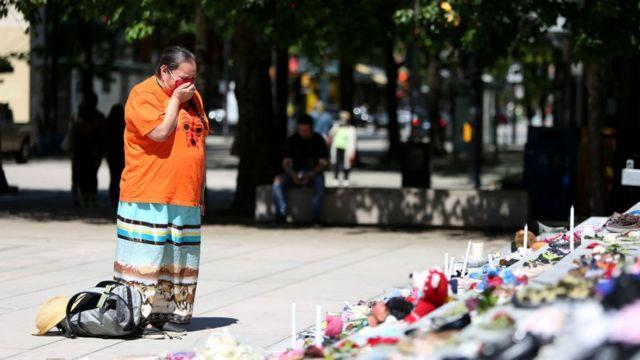 Una donna piange davanti a una veglia in Canada