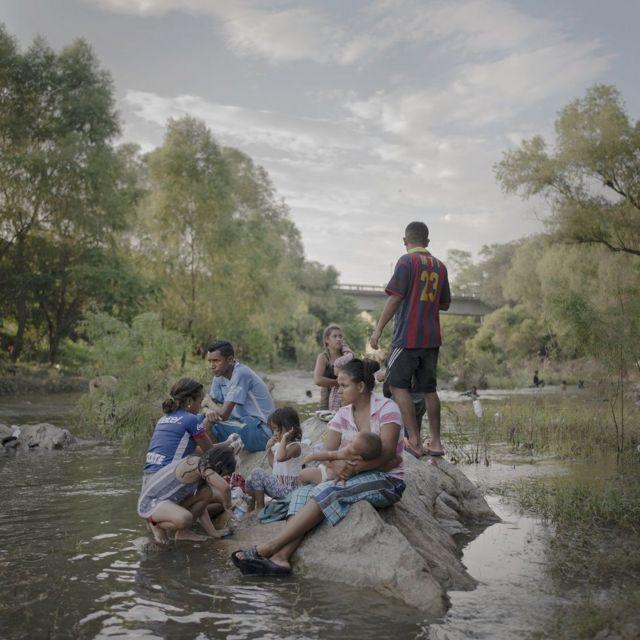 ভিবাসী পরিবার রিও নোভিলেরো নদীর কাছে স্নান করছে এবং, কাপড় ধুচ্ছে।