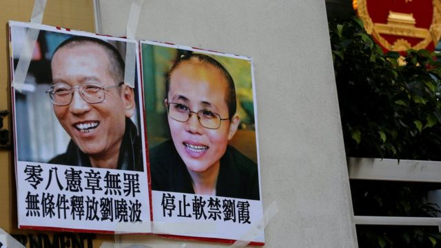 """Photos of Chinese Nobel rights activist Liu Xiaobo (L) and wife Liu Xia are left by protesters outside China""""s Liaison Office in Hong Kong, China June 27, 2017"""
