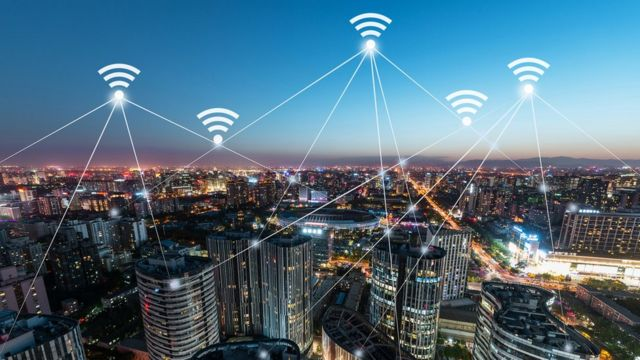 Paisaje nocturno ciudad con señales de wifi.
