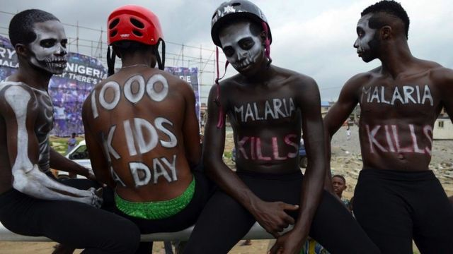 Four men with slogans painted on them take part in an anti-malaria campaign