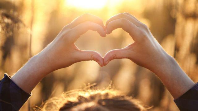 Mujer formando un corazón con sus manos.