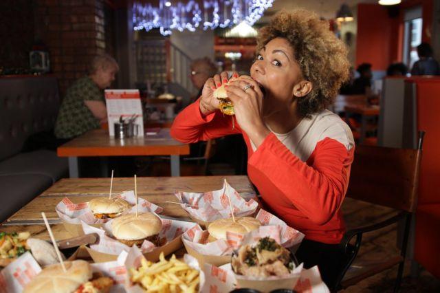 La doctora Zoe Williams comiendo una hamburguesa.