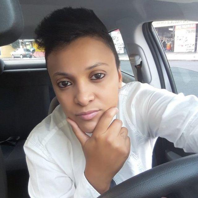 Daniela com a mão no queixo dentro do carro que usava para trabalhar como motorista de aplicativos em São Paulo