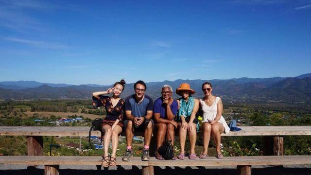 Jô, no centro da imagem, aparece com outras quatro pessoas sentadas em um banco durante viagem para a Tailândia