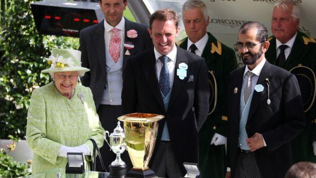 شیخ محمد (سمت راست تصویر) درعکسی با ملکه بریتانیا در یکی از مسابقات اسبدوانی در سال ۲۰۱۹