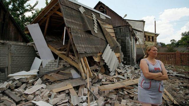 Женищна стоит рядом со своим разрушенным домом в Донецкой области