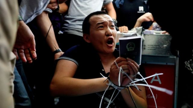 Fu Guohao, reportero del Global Times atado por los manifestantes.
