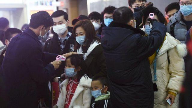 فرق المتابعة الصحية في الصين تقيس درجات حرارة الأشخاص القادمين من مدينة ووهان إلى مدن أخرى في أنحاء البلاد.