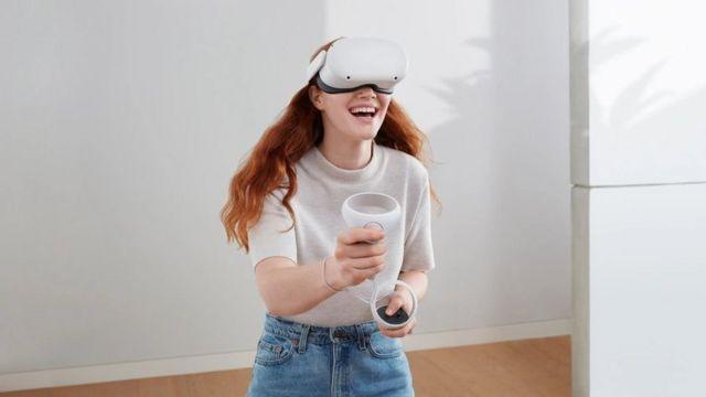 Mulher usa headset Oculus Quest 2 com controle na mão