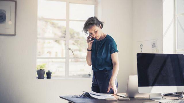Una mujer habla por teléfono parada