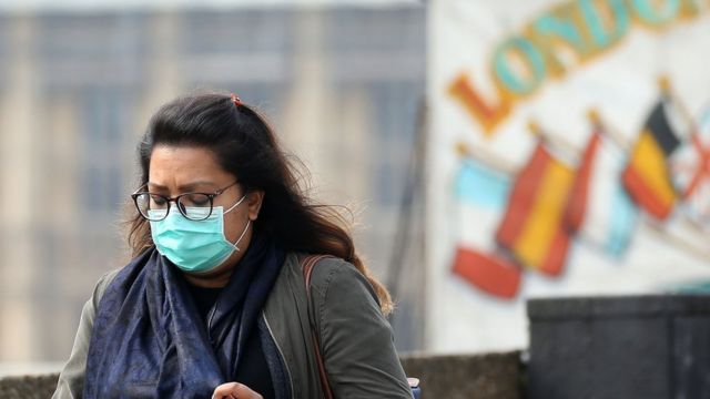 A woman wears a mask in central London