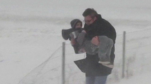 Man carrying child in snow