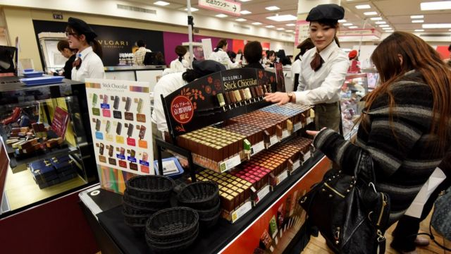 Shoppers buying Valentine's day chocolate in a department store.