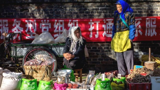 Local women sell produce in the market. Zhongyi market, located at the southern gate of Dayan ancient city, in Lijian, Yunnan Province in China