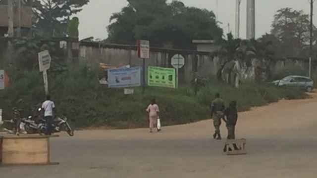 Quelques civils marchent dans la rue, devant les militaires mutins qui ont barré la route