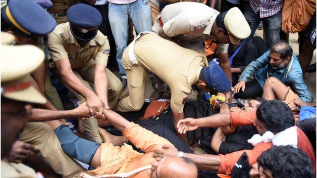 प्रदर्शनकारियों को काबू करने की कोशिश करती पुलिस