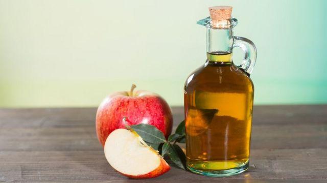 Vidro de vinagre ao lado de maçãs