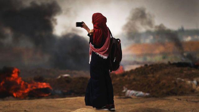 Mulher tira foto do local de confronto entre palestinos e israelenses em Gaza