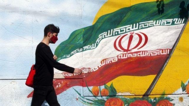 İranlı bir çocuk, İran'ın ulusal bayrağını taşıyan bir duvar resminin yanından geçiyor