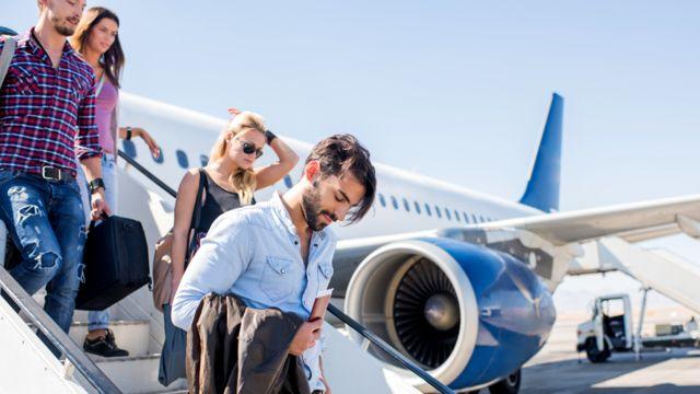 jovens descendo de um avião