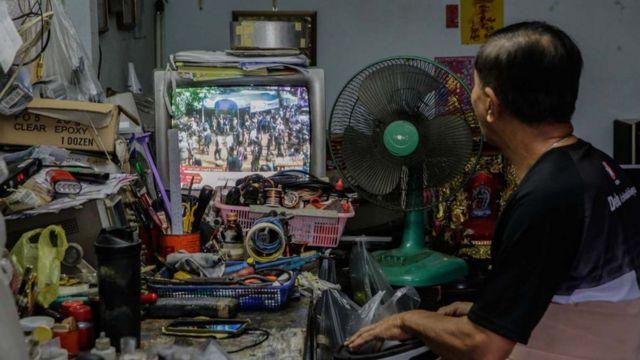 Televizyondan haberleri takip eden bir Taylandlı