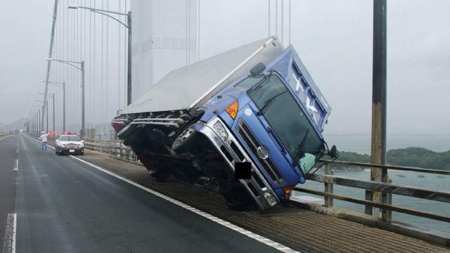 Вантажівка, яку нахилиив вітер, на мосту