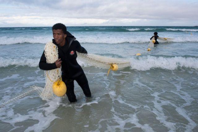 """مراقبو أسماك القرش في شاطئ """"فيش هوك"""" بمدينة كيب تاون بجنوب أفريقيا يسحبون شبكة توضع كحاجز لحماية الناس من هجمات القرش في مناطق السباحة العمومية."""