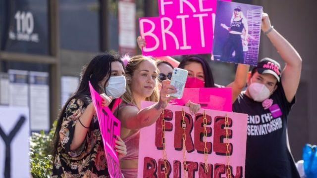 """Seguidores de Britney Spears afuera de una corte con carteles que dicen """"Liberen a Britney""""."""