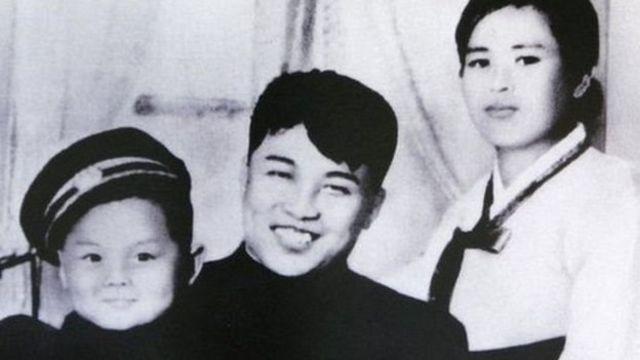 อดีตผู้นำคิม จอง อิล (ซ้าย) ในวัยเด็ก ถ่ายภาพร่วมกับบิดาและมารดา