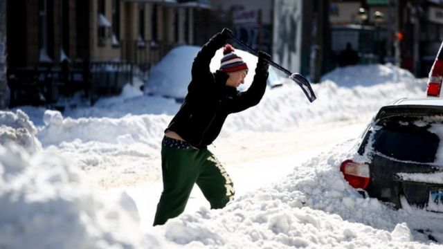 ニューヨークで雪に埋もれた車を書き出そうとする男性(24日)