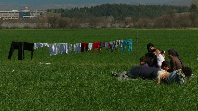 Family lies near their washing as it dries on a line in a field