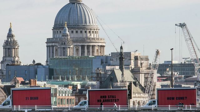 The three vans with the billboards passing over a bridge near St Paul's Cathedral