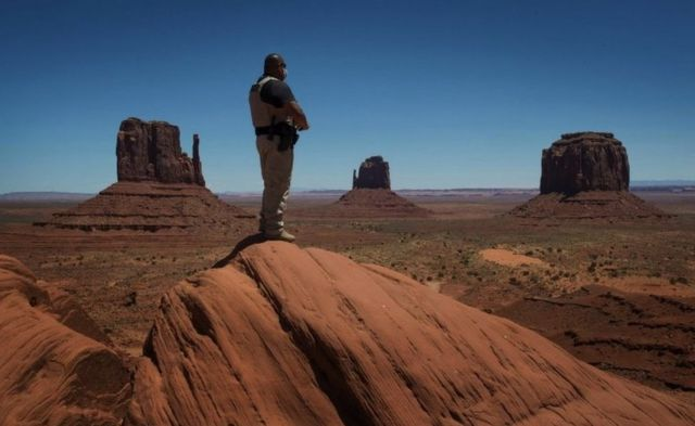 A Navajo park ranger looks out over Navajo Nation-managed Monument Valley