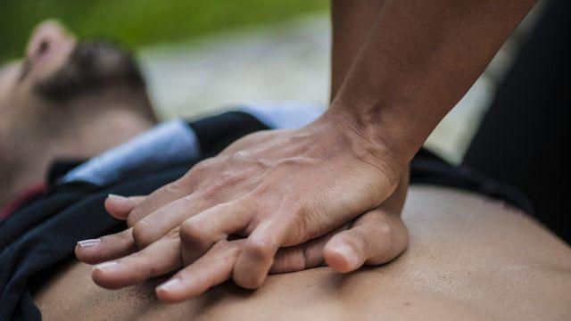 kalp masajı yapan bir adam.