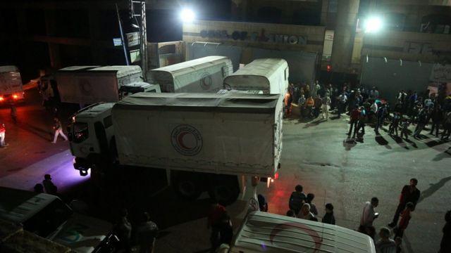 Los trabajadores de ayuda descargan abastecimientos de comida y humanitarios en la ciudad de Madaya