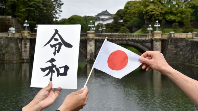 """People hold a flag of Japan and a board bearing new era name """"Reiwa"""" near the Double Bridge at the Imperial Palace in Tokyo on May 1,"""