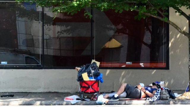 Imagem mostra homem sem teto deitado em uma calçada em Portland, nos Estados Unidos
