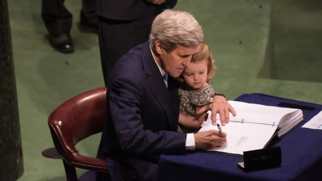 John Kerry firmando el acuerdo de París sobre cambio climático con su nieta en 2016.