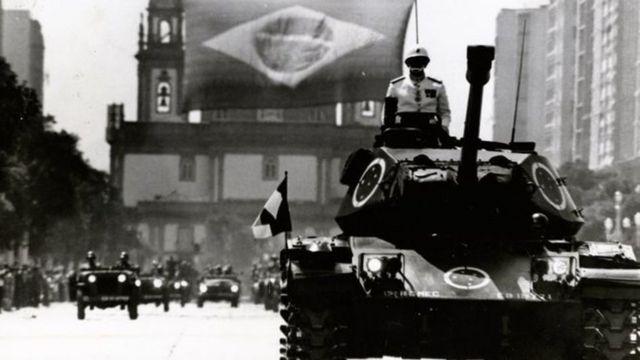 Foto em preto e branco mostra tanque na rua com militar em cima