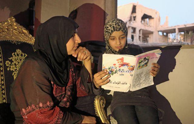 Islam leyéndole un libro a su madre.