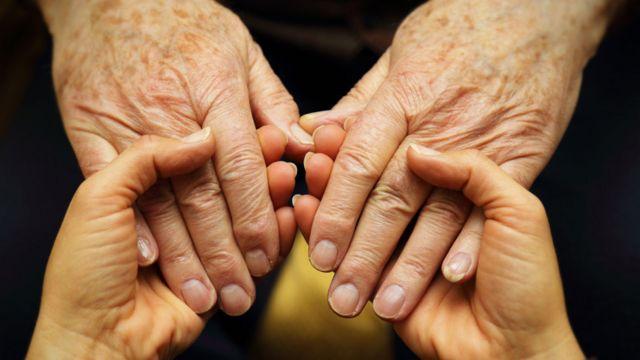 Dos personas de manos dadas