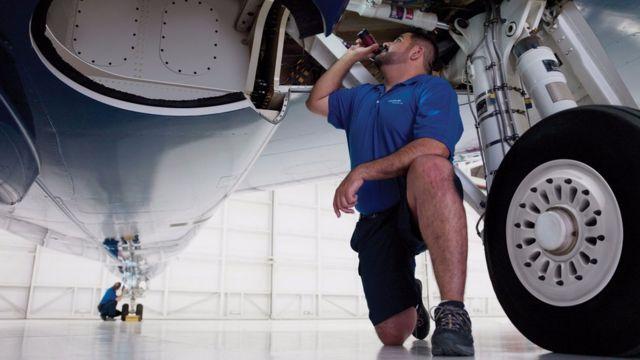 Homem olha debaixo de avião com lanterna