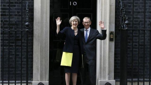 夫フィリップ・メイ氏と官邸玄関前で報道陣に笑顔を見せるメイ新首相